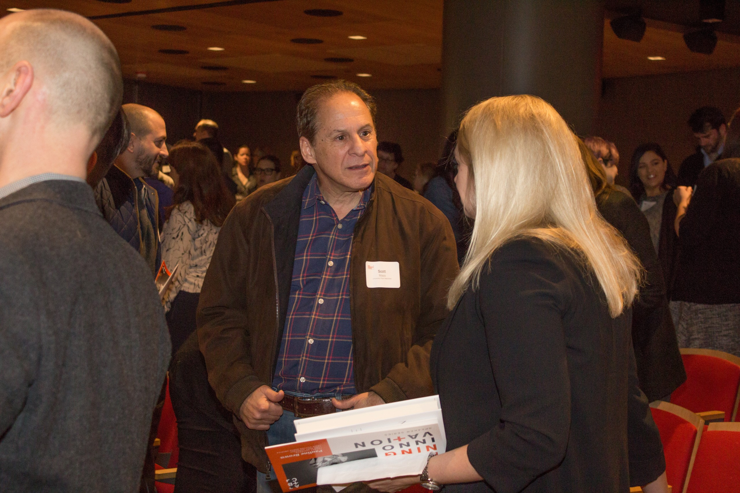 Photo of Defining Innovation speaker talking with attendee